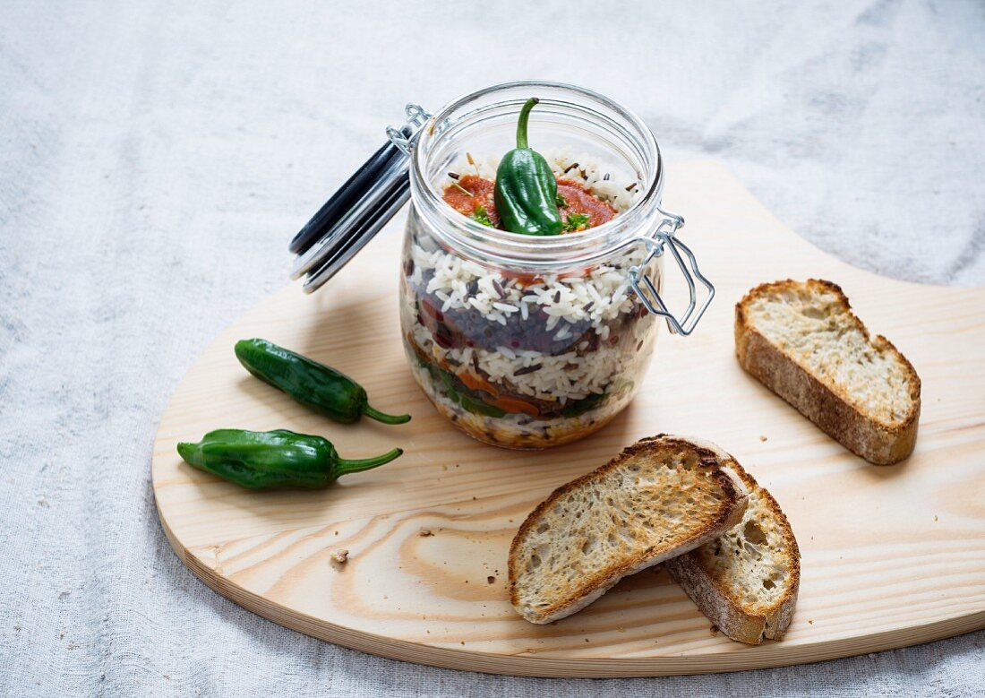 Rice, tomato sauce, fried peppers, soy meat, kidney beans and lentils in a glass jar, served with toasted bread