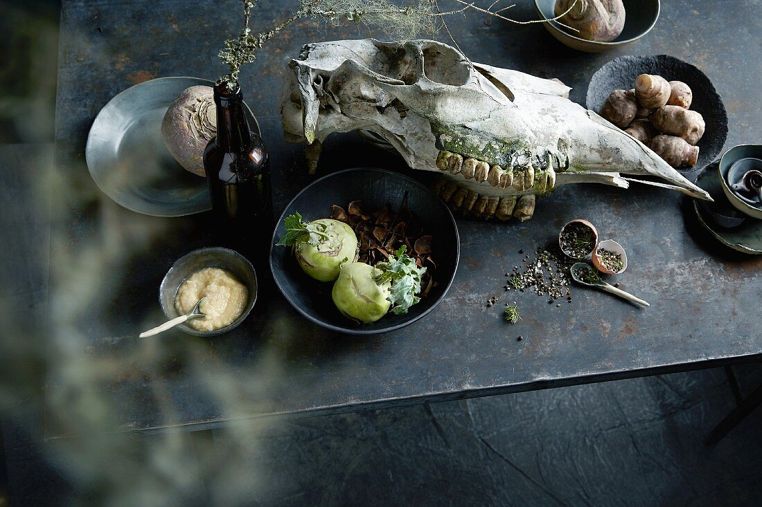 Beetroot, kohlrabi, celery cream, spices and an animal skull on a table