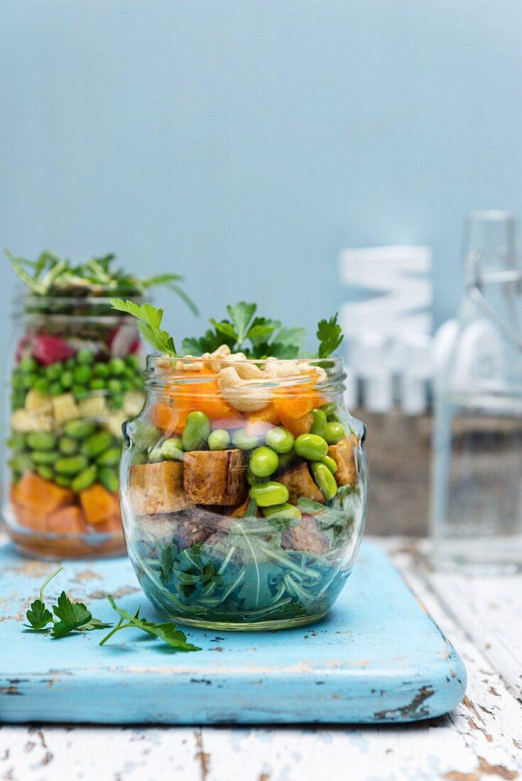 Vegan crispy tofu salad with vegetables and cashews in a glass jar