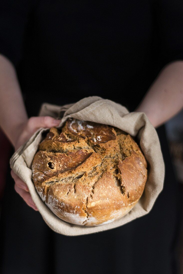 Hands holding clay pot baked beer bread