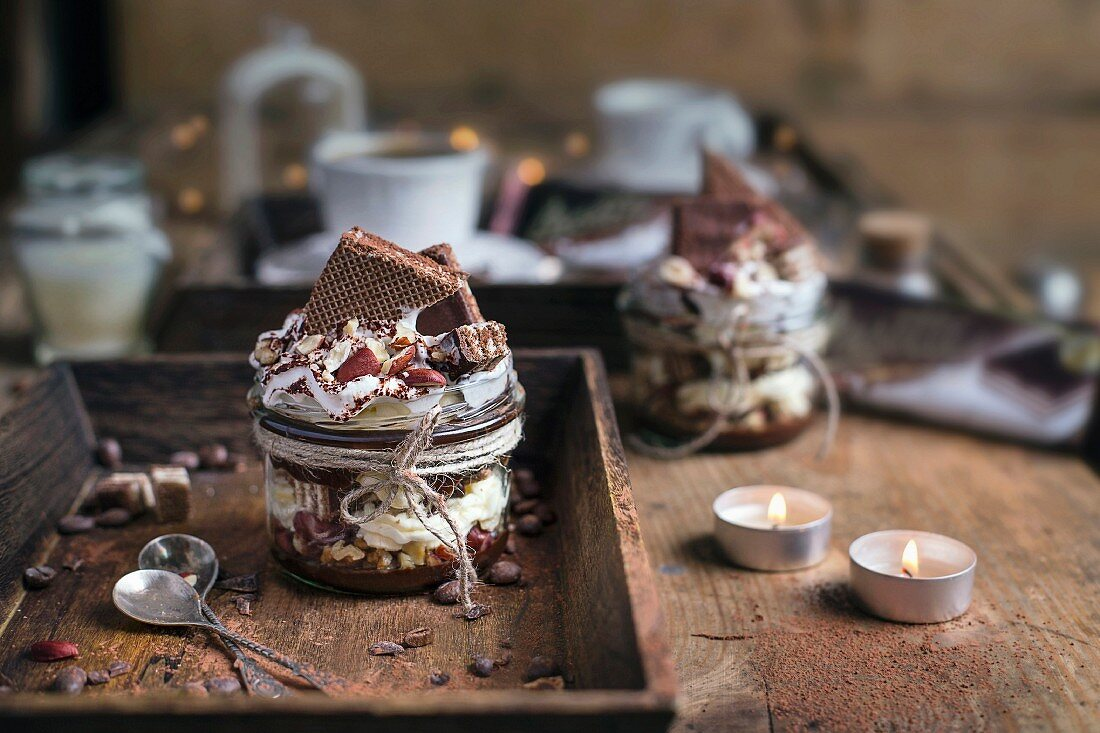 Dessert with Mascarpone, Chocolote and Hazelnuts, topped with cocoa powder and whipped cream served on a wooden table