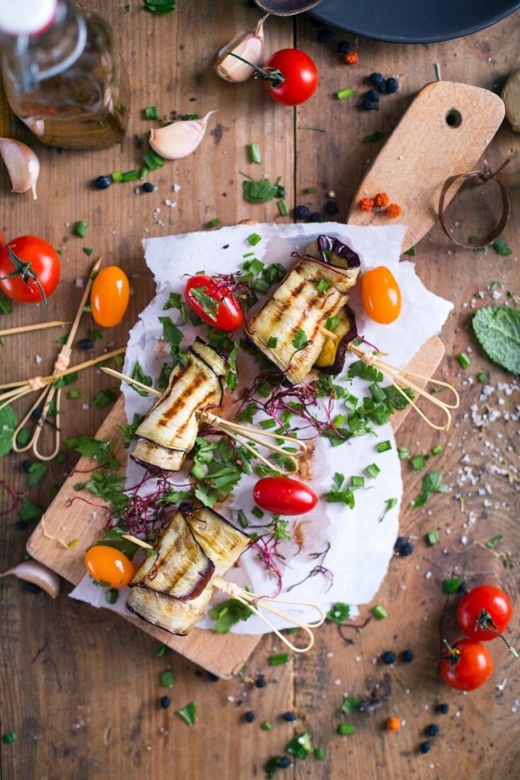 Grilled Aubergine with tomatoes and chives on a cutting board