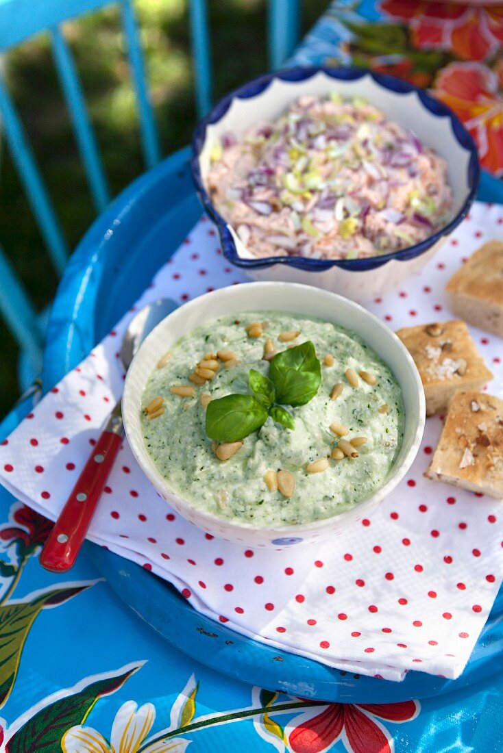 Cold basil soup with pine nuts, creamy tuna sauce and leeks on a table outdoors