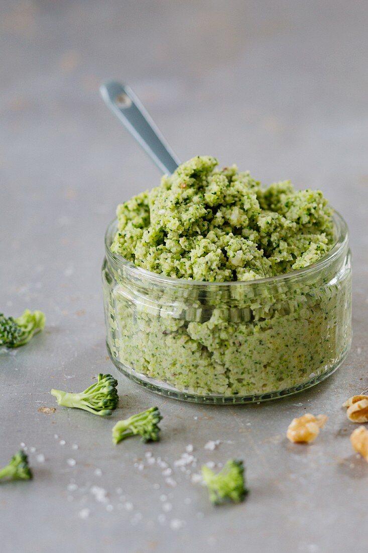 Broccoli and walnut pesto in a glass ramekin with a ceramic spoon