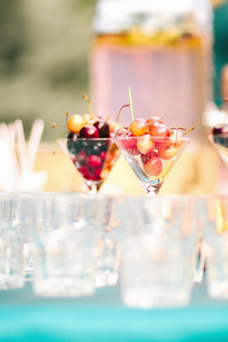 Glasses with different cherries on a garden table