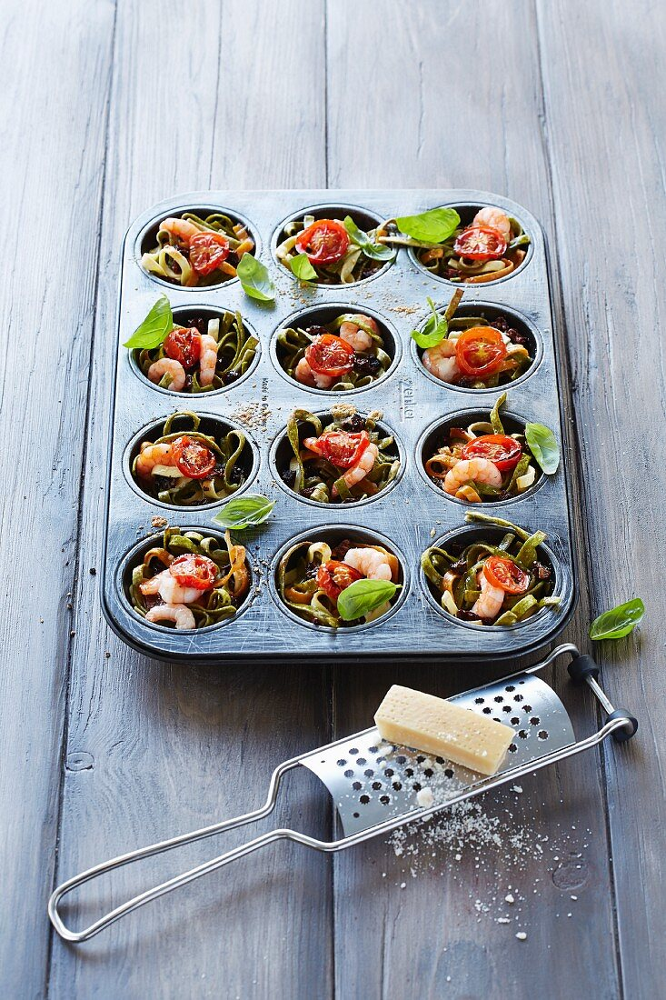 Noodles with shrimps and tomatoes in a muffin tray