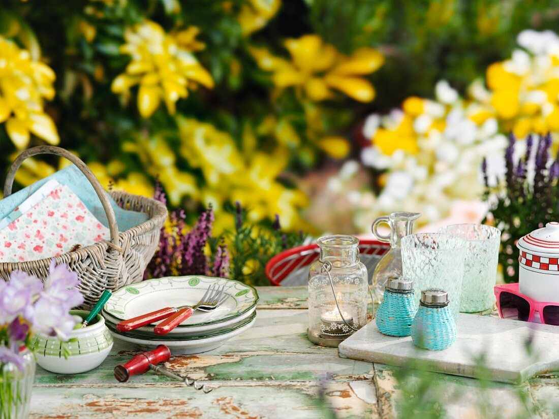 A basket, crockery, a lantern, glasses and salt and pepper shakers on a table in a summery garden