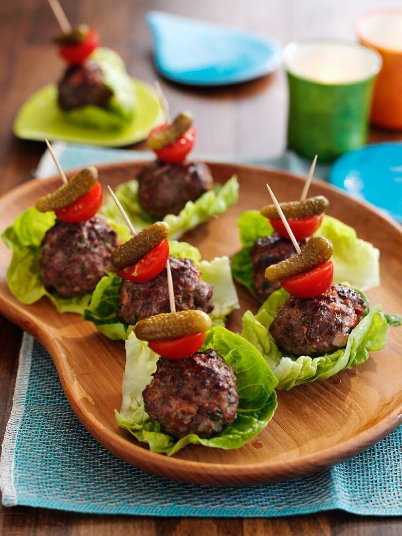 Bacon beef sliders with tomato and mini gherkins on lettuce leaves