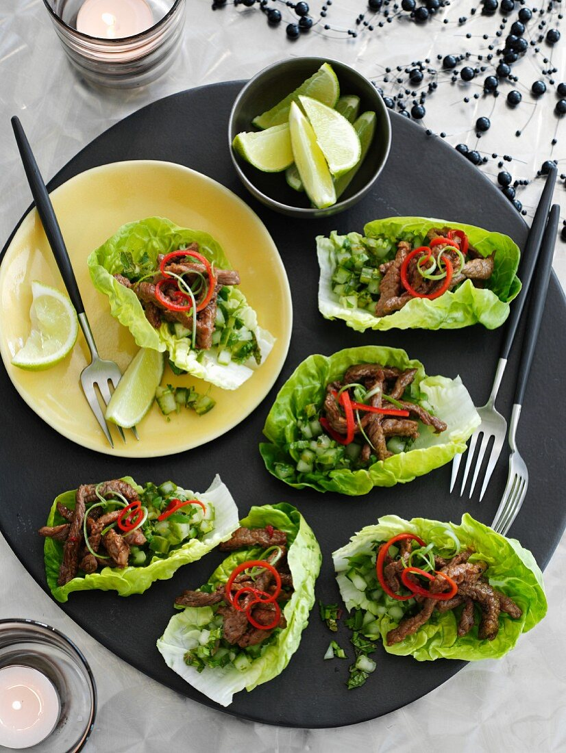 Beef strips with cucumber salsa served in lettuce leaves