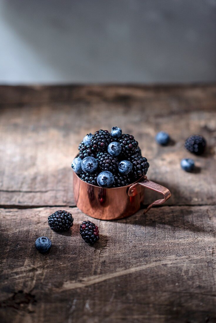 Blueberries and blackberries in a copper measuring cup