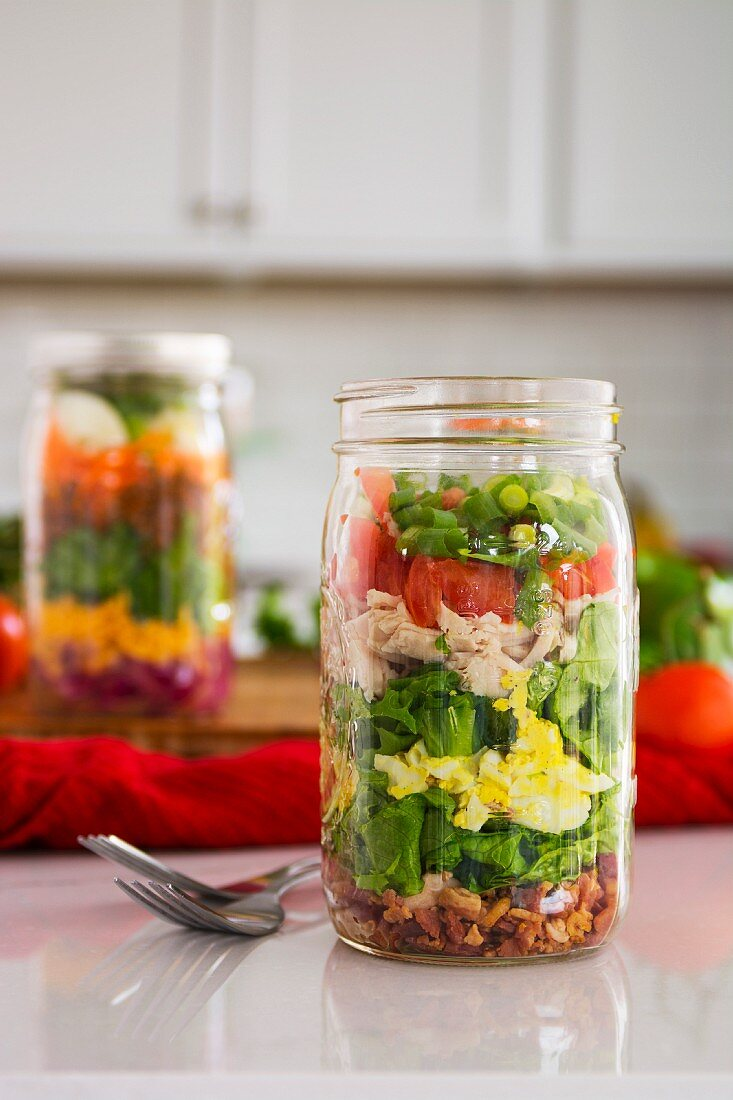 Layered salad in glass with spinach, beans, cheese and egg