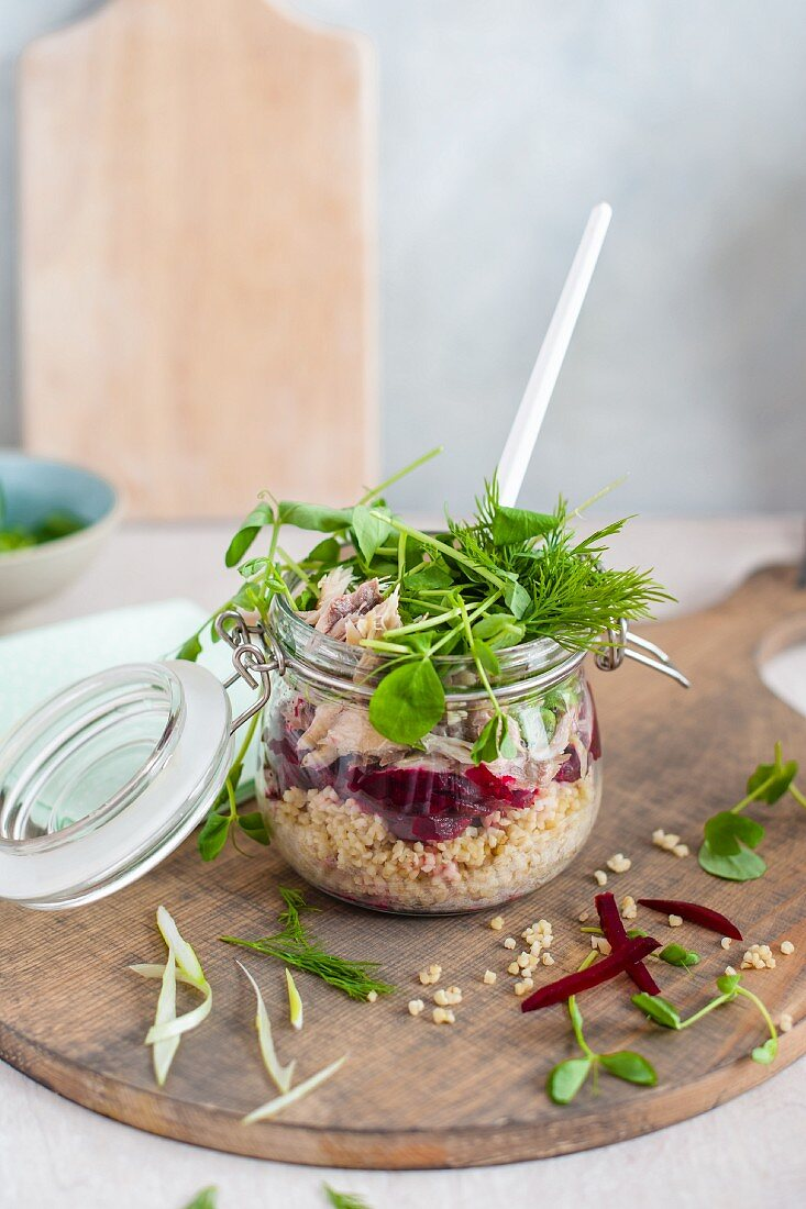 Bulgur with mackerel, beetroot, pea sprouts and dill served in a glass jar