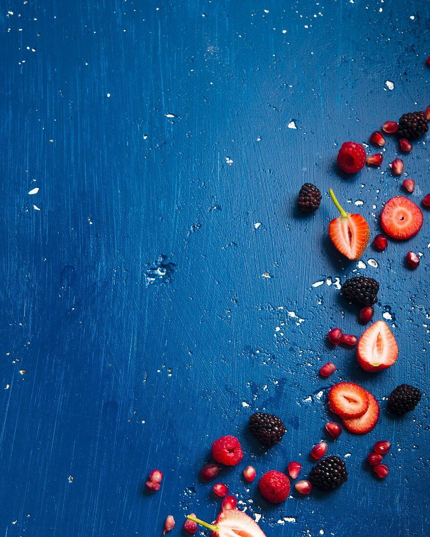 Various berries and pomegranate seeds on a blue background