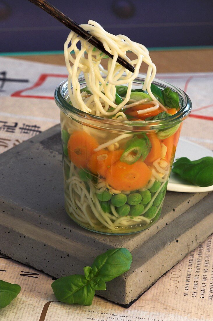 Asian noodle soup with peas, carrots and basil in a glass