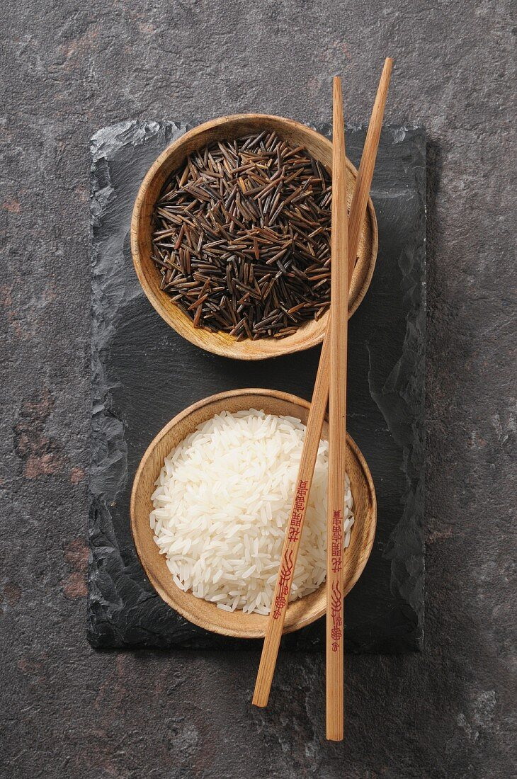 White and black rice in small bowls (top view)