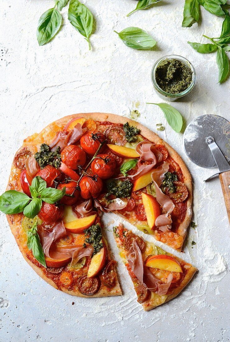 Spelt pizza with tomatoes, ham, nectarines and kale pesto