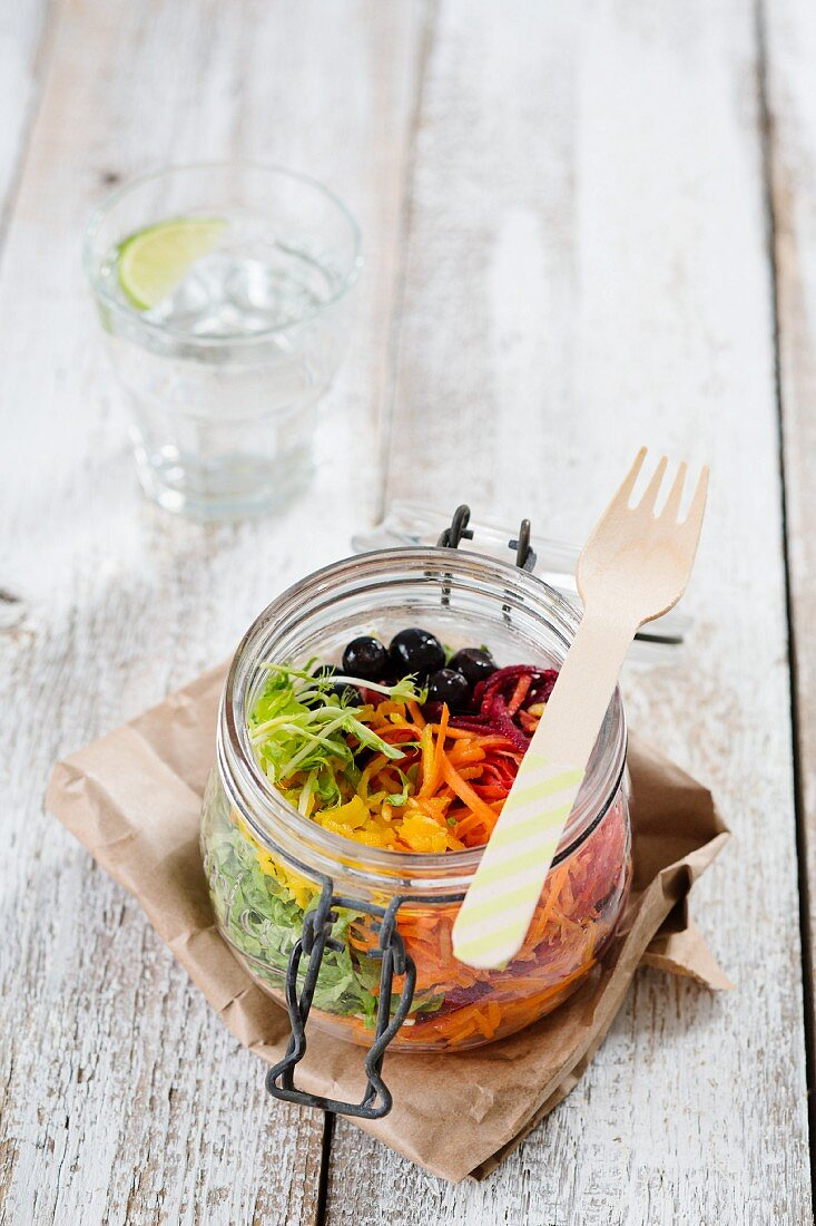 Rainbow salad in an open glass jar with beetroot, carrots, yellow pepper, lettuce and blueberries