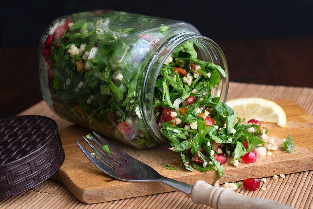 Millet taboule in a glass jar with pomegranate seeds, parsley and mint