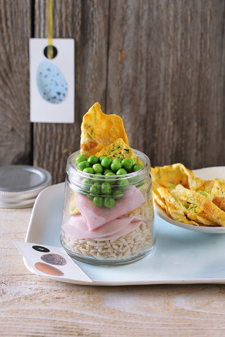 Brown rice salad with omelette, ham and peas in a glass jar