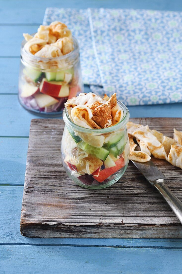 Apple and cucumber salad with pancake strips in a glass jar