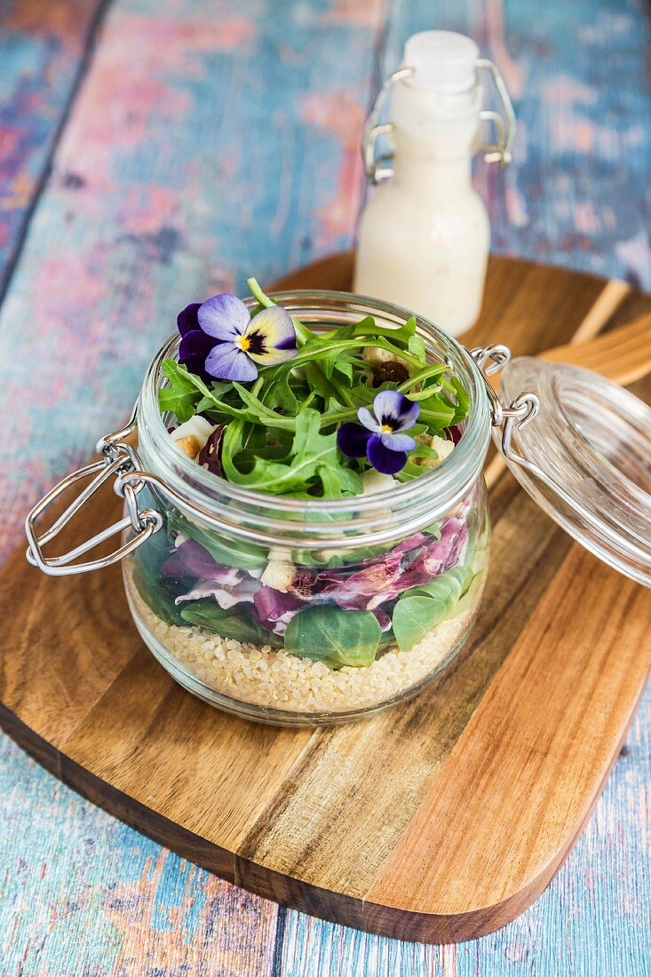 A quinoa salad with lambs lettuce, radicchio, rocket, croutons, goat's cheese and horned violets in a glass jar on a wooden board, with dressing in a glass bottle