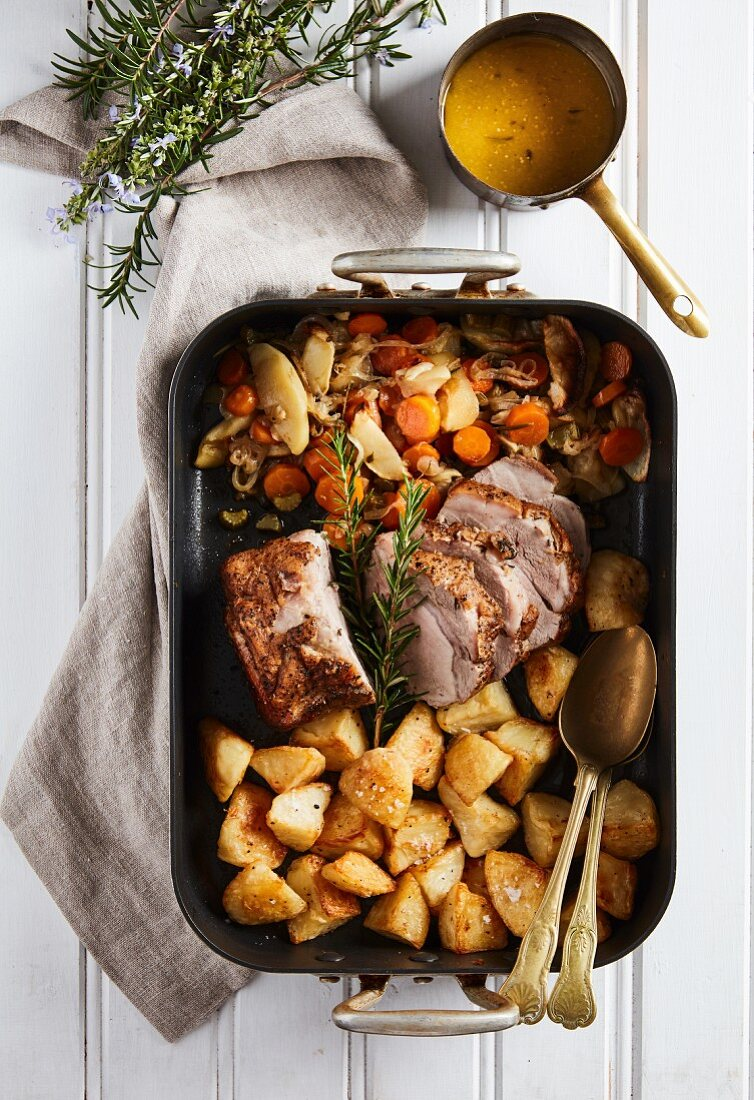 Roast pork with baked potatoes, apple, vegetables and cider sauce