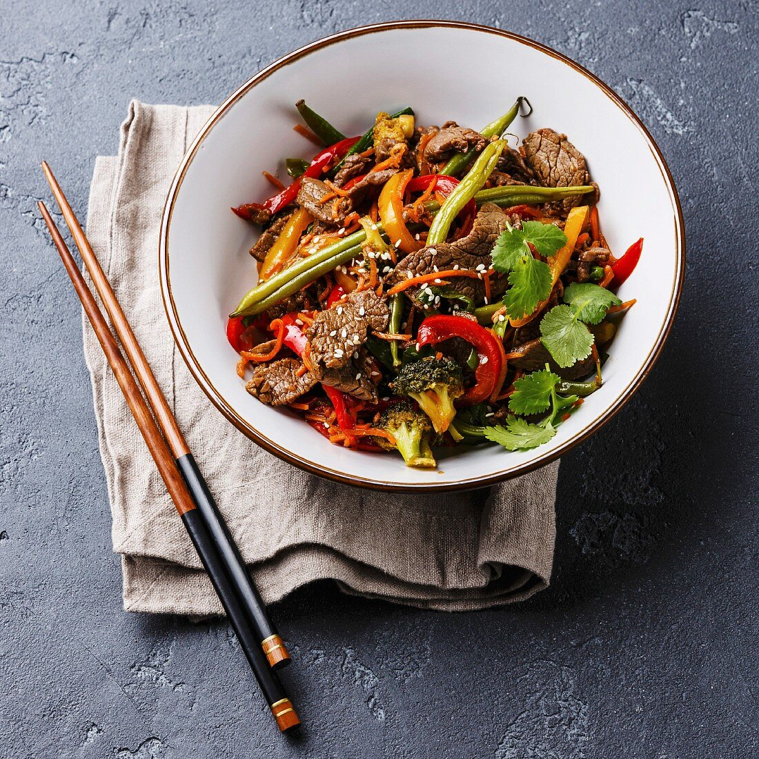 Szechuan beef stir fry with vegetables in bowl on dark stone background