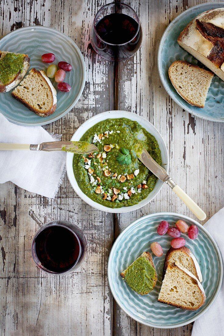 Gorgonzola Hazelnut Cilantro Pesto served in a ceramic bowl with crostini, grapes and wine
