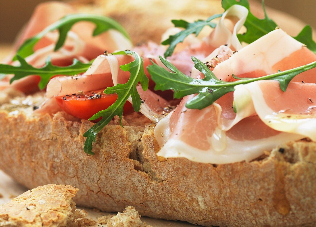 A panini with prosciutto, tomatoes and rocket