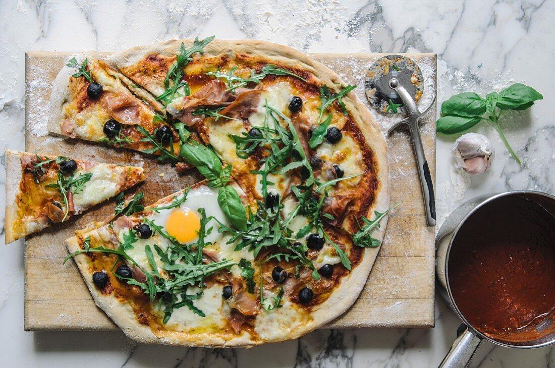 Pizza mit Tomatensauce, Spiegelei, Rucola, Oliven und Parmesan (Aufsicht)