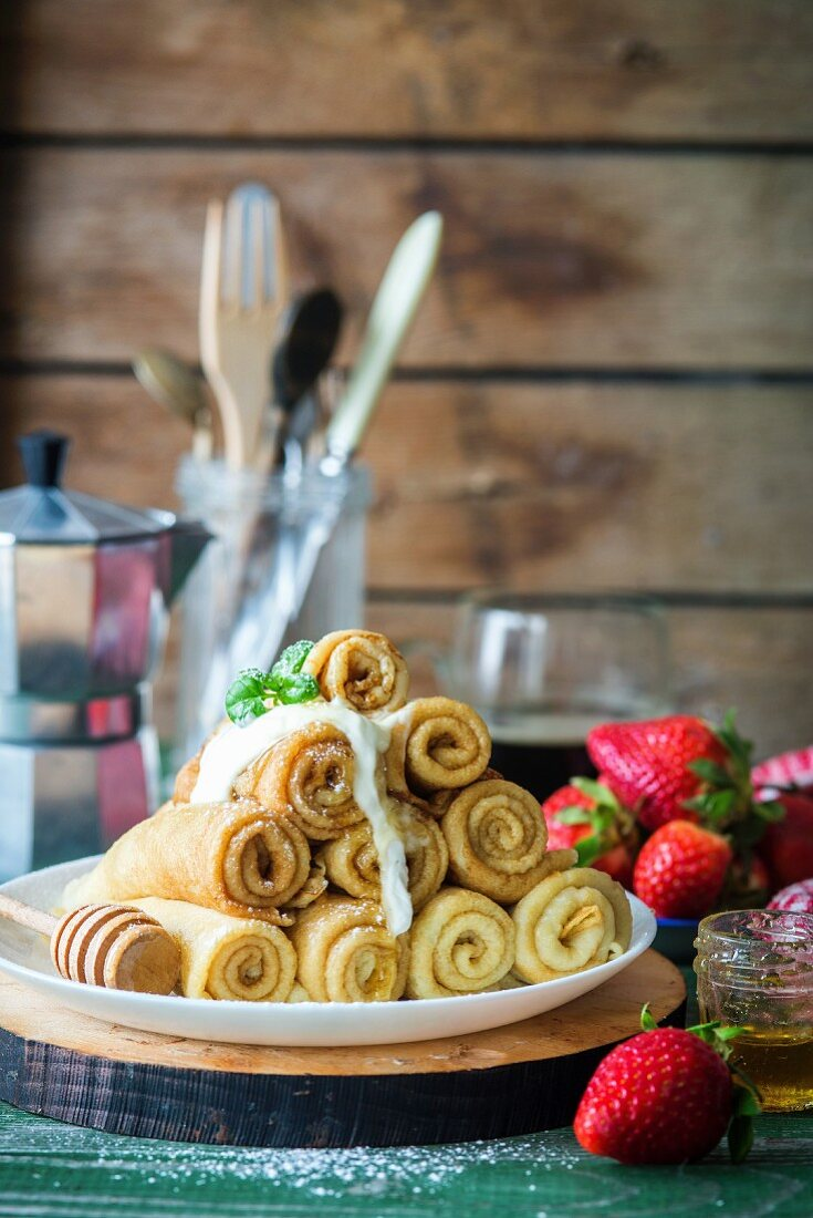 Rolled crêpes with honey and strawberries