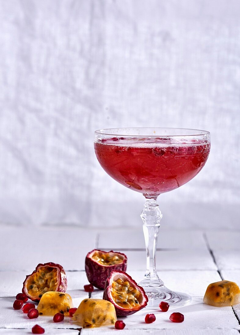 A sparkling wine cocktail with passion fruit and pomegranate