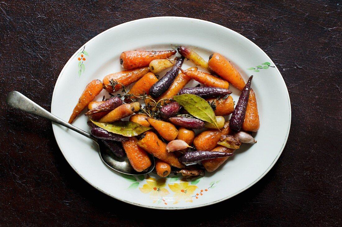 Glasierte bunte Karotten mit Knoblauch, Lorbeer und Thymian (Aufsicht)