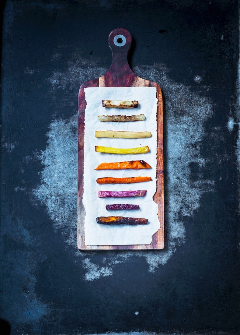 Various vegetable fries lined up on paper on a wooden board