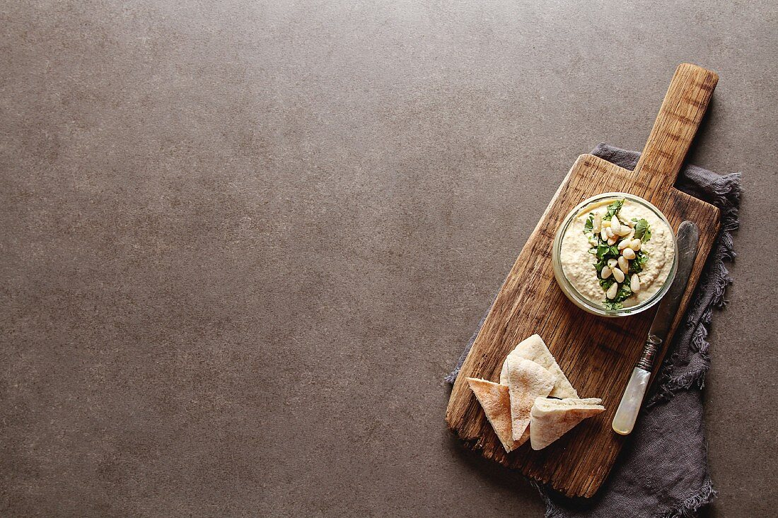 Classic hummus with herbs, olive oil in a glass jar and lavash, Traditional Middle Eastern cuisine