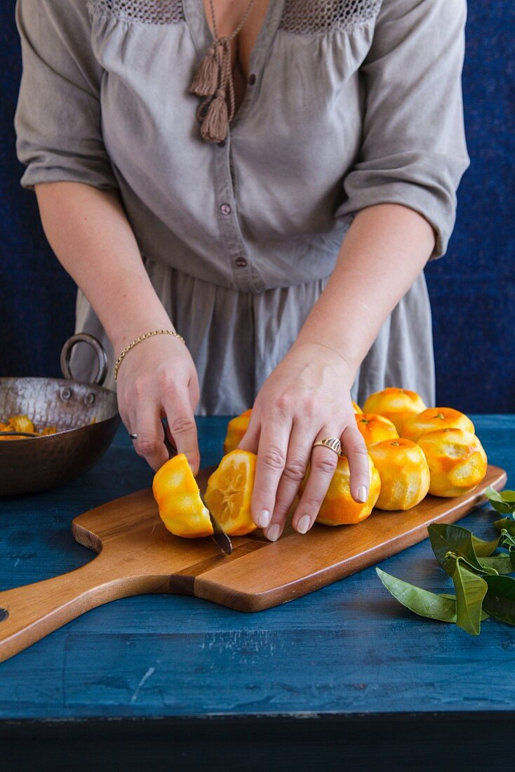 A woman halving oranges