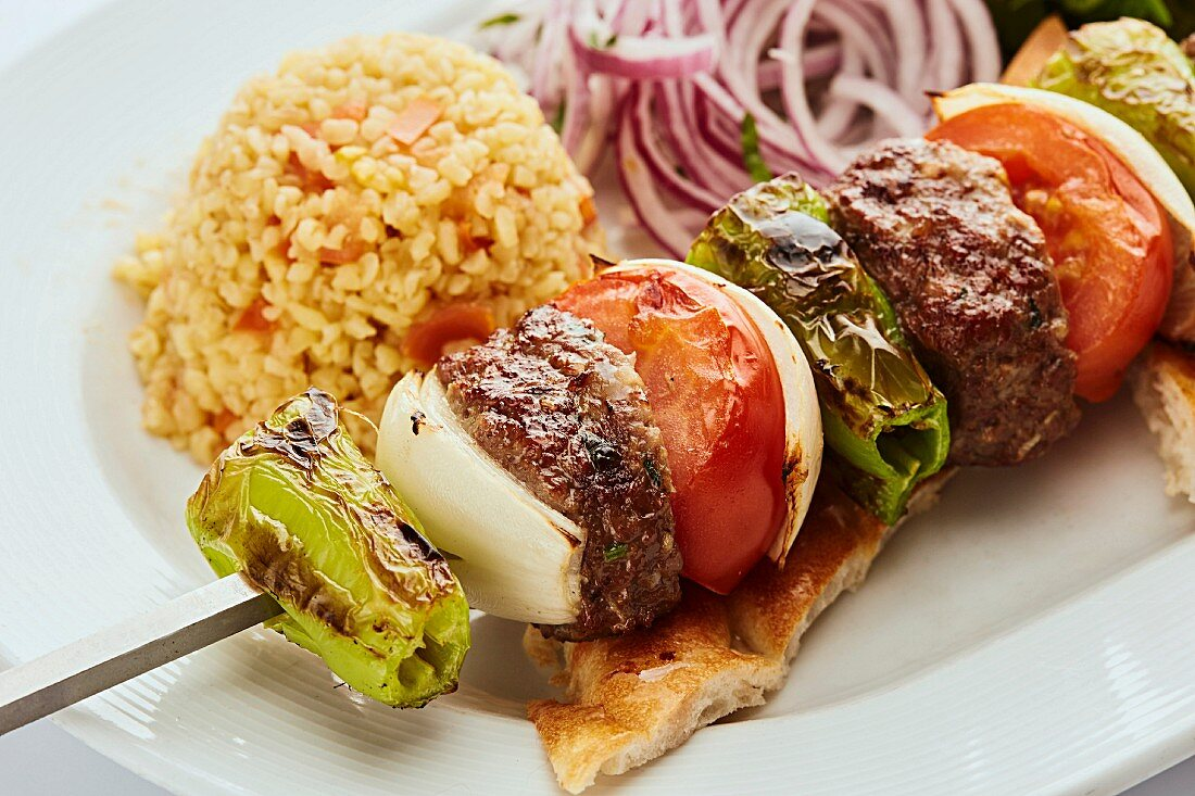 Minced beef skewer with onion, green pepper and tomato served with rice and flatbread