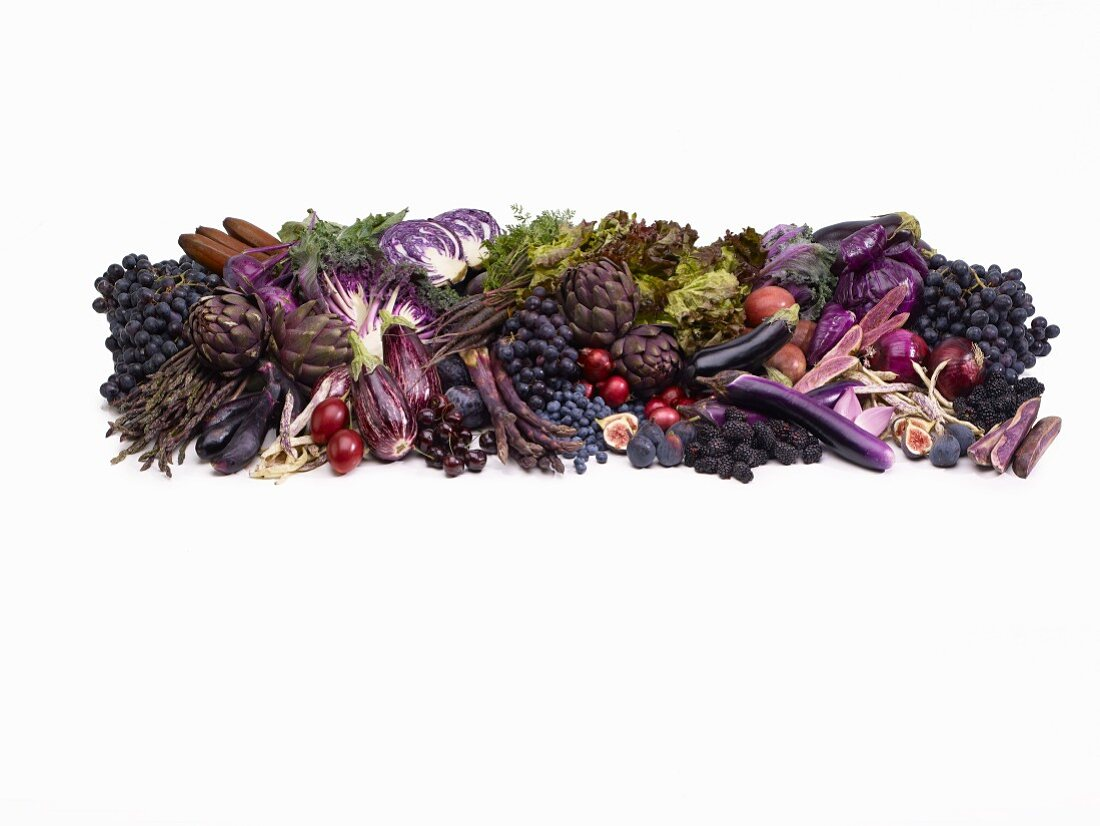 Purple fruit and vegetables in front of a white background
