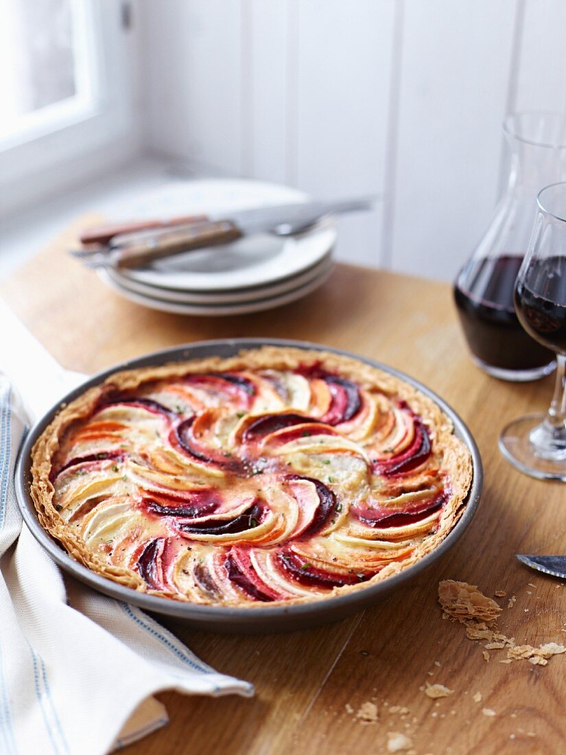 A glass and a carafe of red wine next to a root vegetable tart in a baking tin