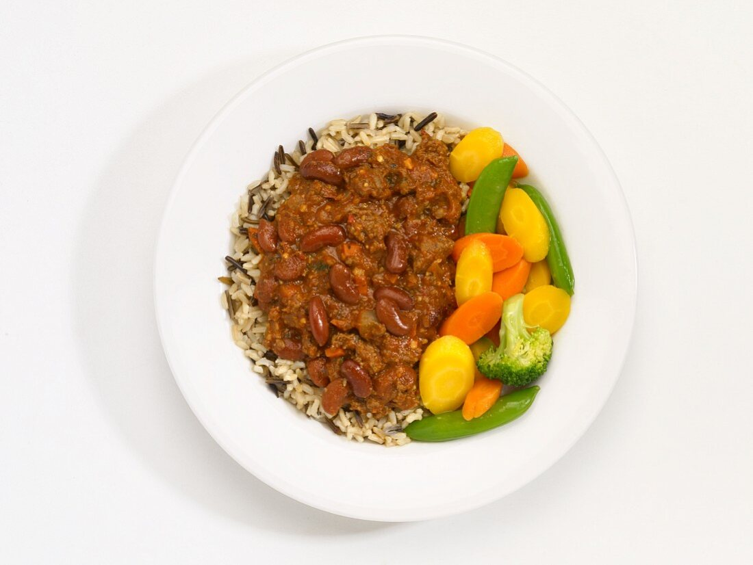 Low-fat chilli with vegetables and rice on a plate in front of a white background (seen from above)
