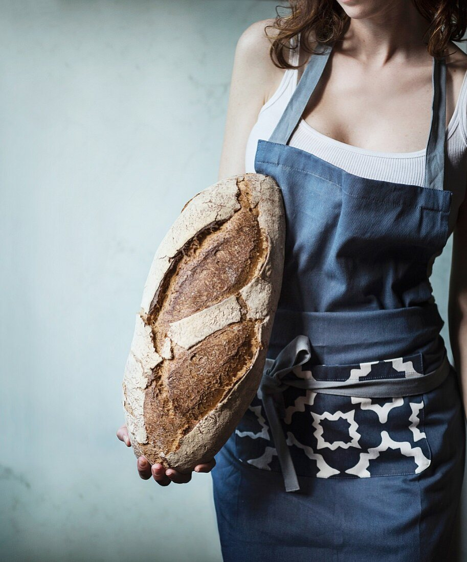 Frau mit Schürze hält Brotlaib in der Hand