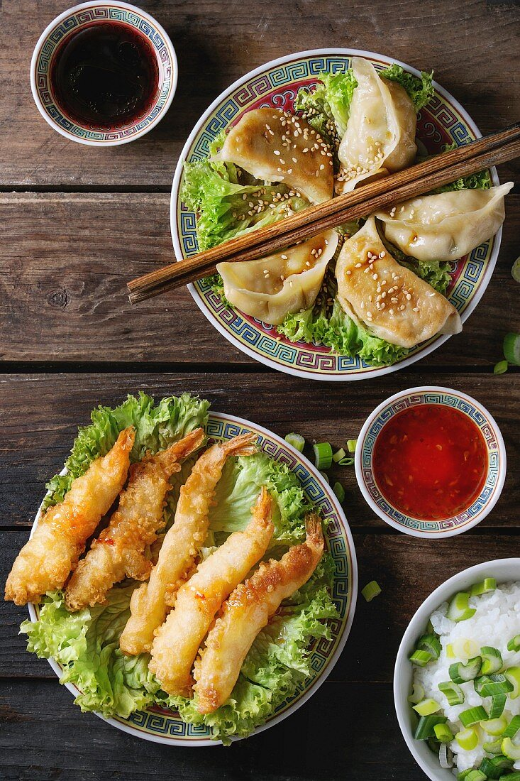 Fried tempura shrimps and gyozas potstickers on lettuce salad with sauces and rice