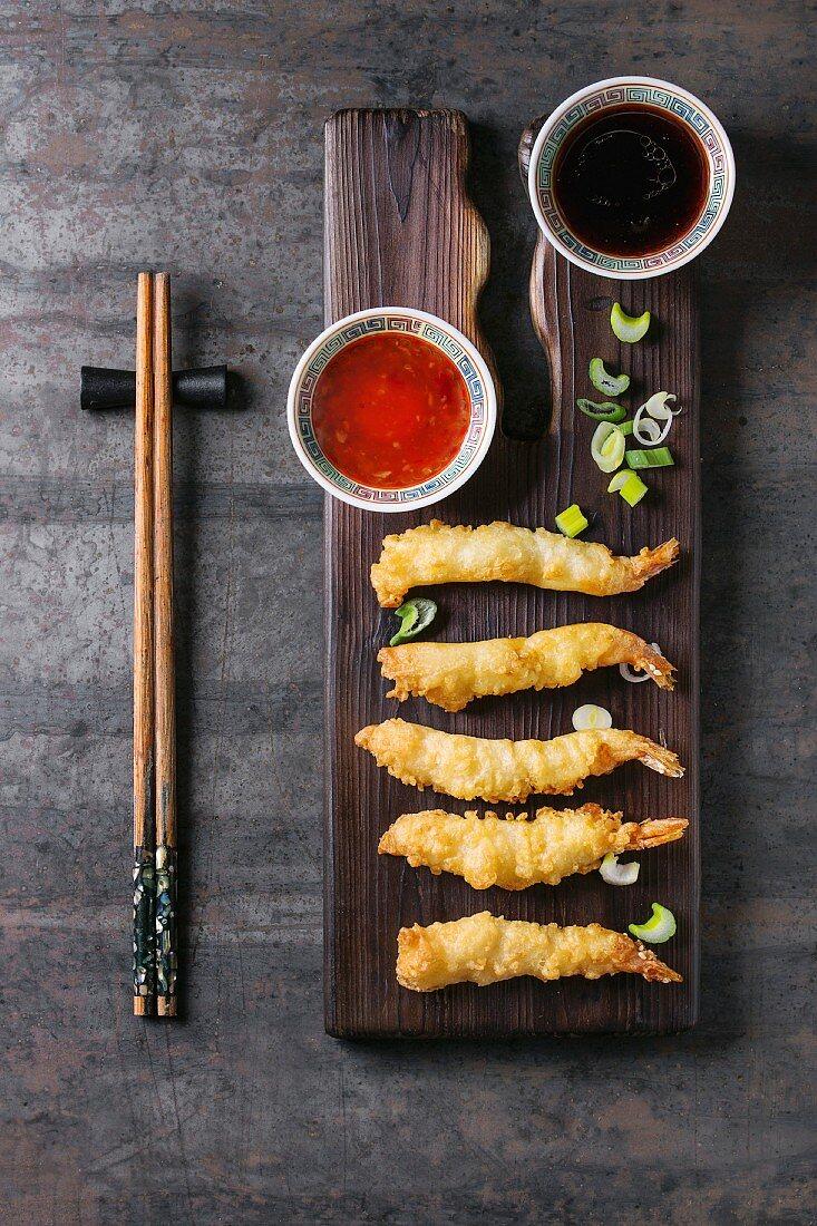 Fried tempura shrimps on lettuce salad with sauces