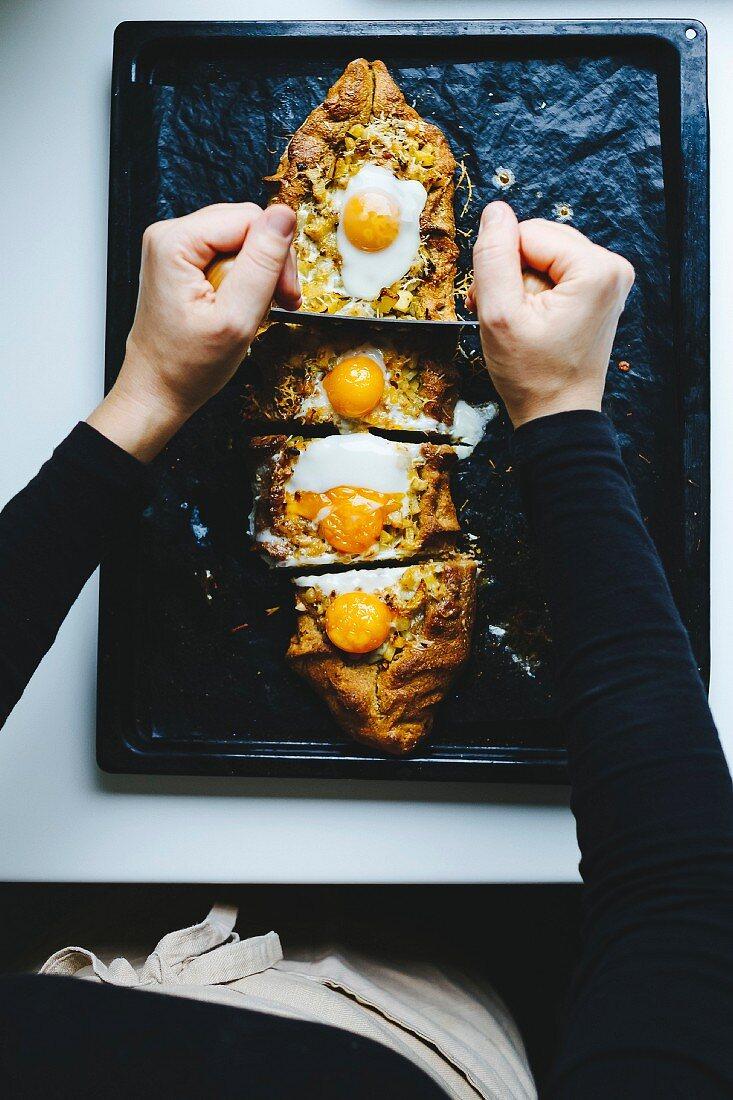 Girl cutting potato and egg pie