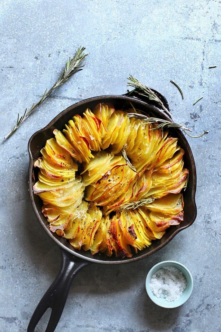 Crispy leaf potato roast on a frying pan, seasoned with salt and black pepper