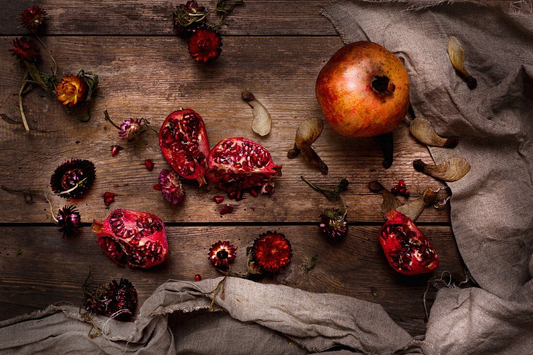 Whole and broken pomegranates with everlasting flowers and maple seeds (top view)