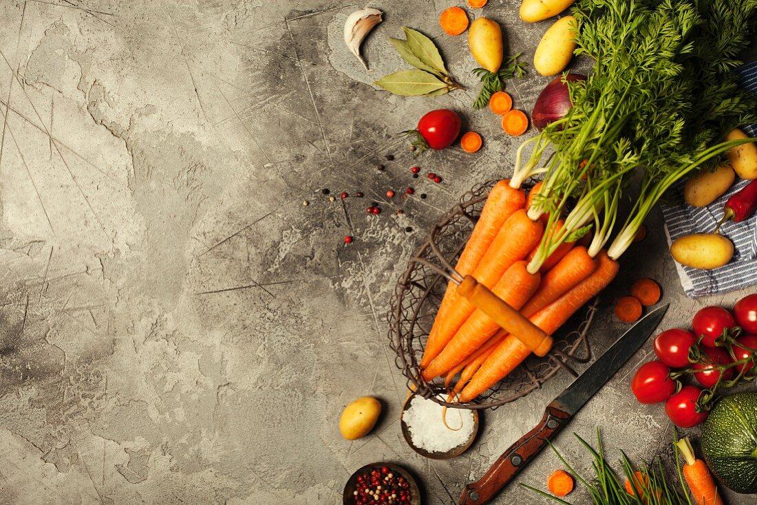 Frische Karotten und Gemüse auf rustikalem grauen Steinuntergrund