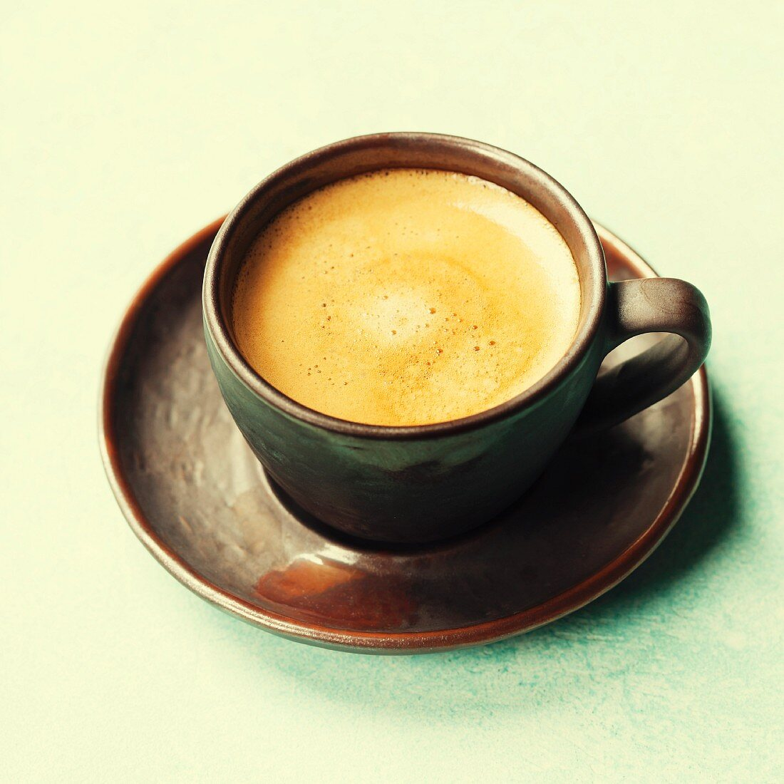 Cup of aromatic coffee over vintage table close up