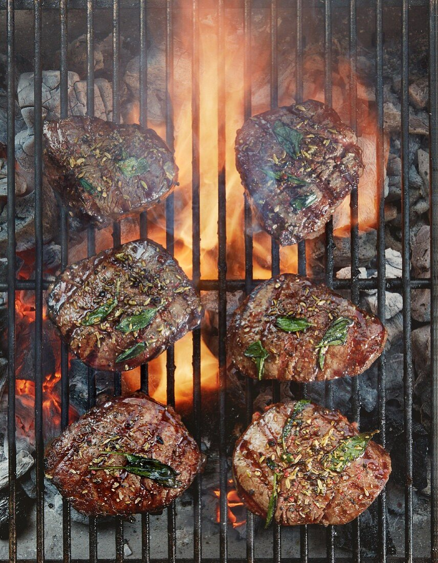 Beef fillets with sage on a grill (top view)