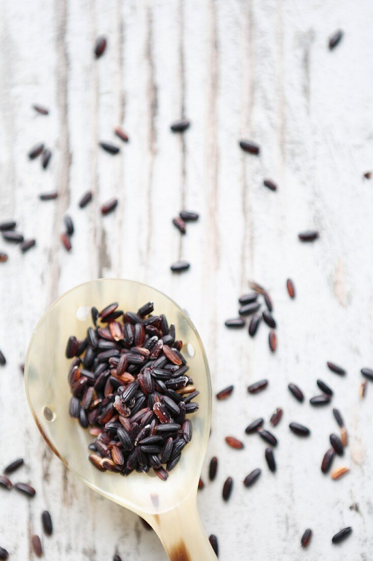 Black rice on a spoon and a wooden background (seen from above)